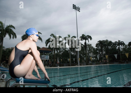 Side profile of a young woman squatting on a starting block - Stock Photo