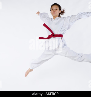 Portrait of a young woman jumping and practicing martial arts - Stock Photo