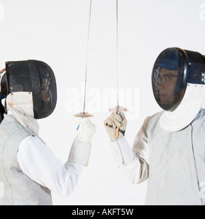 Close-up of a man and a woman wearing fencing masks and holding fencing foils - Stock Photo