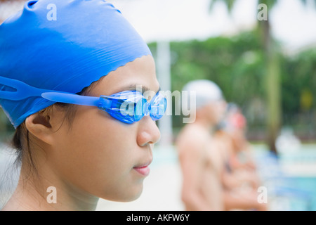 Close-up of a young woman wearing swimming goggles and standing at a poolside - Stock Photo