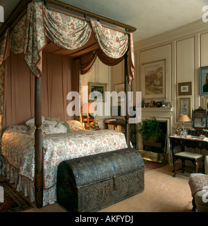 Swagged floral caonpy on four poster bed in cream panelled country bedroom with studded antique chest - Stock Photo