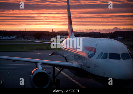 Sunrise over British Airways Airbus A319-131 G-EUPM Chatham Historic Dockyard (21451) plane at Aberdeen Airport, - Stock Photo