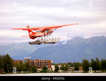 Cessna 206 floatplane taking to the sky as it takes off from Lake Hood Floatplane Base in Anchorage Alaska for a - Stock Photo