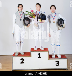 Portrait of three young women in fencing costumes standing on a winner's podium - Stock Photo
