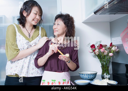 Senior woman preparing food with her granddaughter standing behind her and smiling - Stock Photo