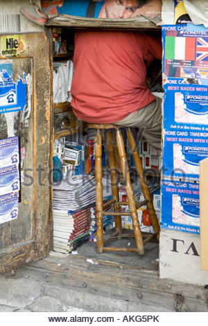 a man sat on a stool in a kiosk in athens greece - Stock Photo