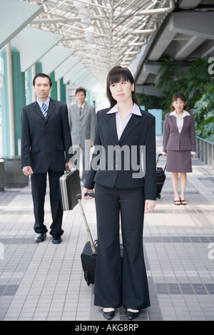 Businesswoman standing and holding his luggage with three business executives in the background - Stock Photo