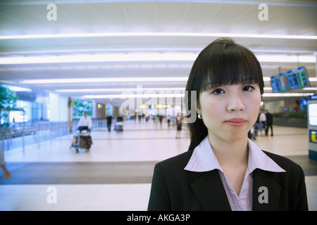 Portrait of a businesswoman at an airport - Stock Photo