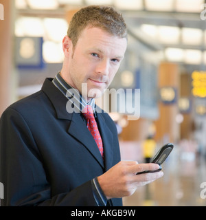 Portrait of a businessman using a mobile phone at an airport lounge - Stock Photo