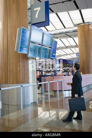 Side profile of a businessman looking at an arrival departure board at an airport - Stock Photo
