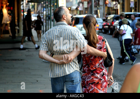 A couple stroll along a busy street in New Orleans with their arms entwined - Stock Photo