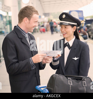 Businessman and a female pilot looking at each other and smiling - Stock Photo