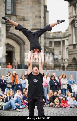 Female acrobat balancing upside down on shoulders of partner at Edinburgh Festival Fringe - Stock Photo