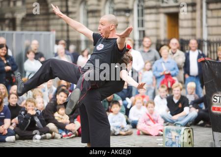 Male acrobat balancing on back of partner at Edinburgh Festival Fringe - Stock Photo