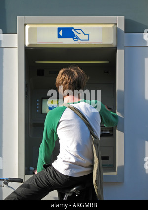Rear view of a young man withdrawing cash at bank's ATM, Colmar, Alsace, France - Stock Photo
