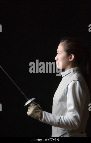 Side profile of a female fencer holding a fencing foil