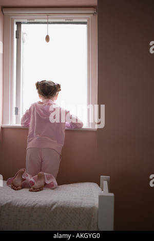 Girl looking out of window - Stock Photo