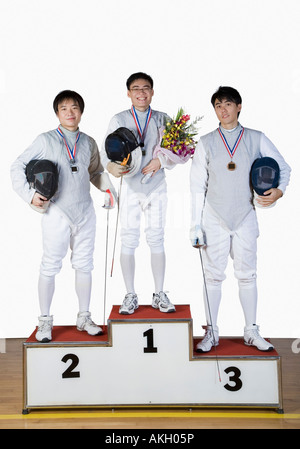 Portrait of three young men in fencing costumes standing on a winner's podium - Stock Photo