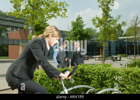 Woman on bike, two businessmen on background - Stock Photo