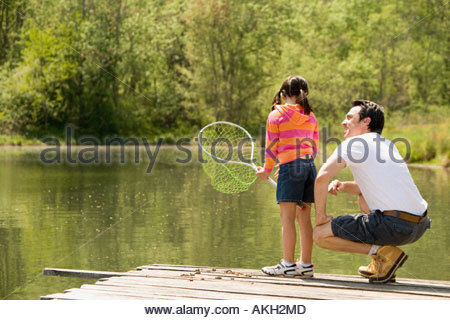 Father crouching next to daughter on jetty, holding fishing net - Stock Photo