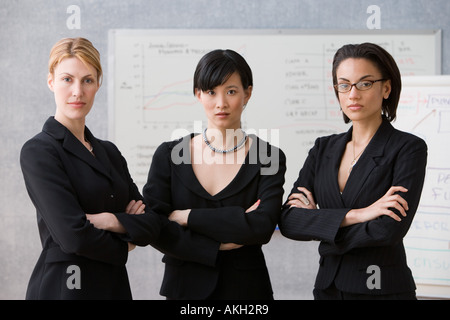 Three young women in lecture theatre - Stock Photo