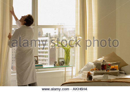 Man opening bedroom curtains - Stock Photo