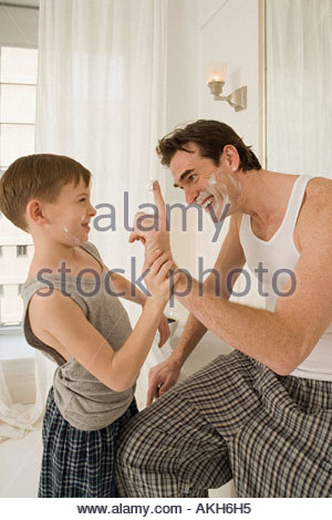 Father and son with shaving cream - Stock Photo