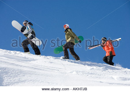 Skiers and snowboarders going up mountain - Stock Photo