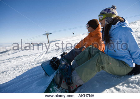 Snowboarders sitting on slope - Stock Photo