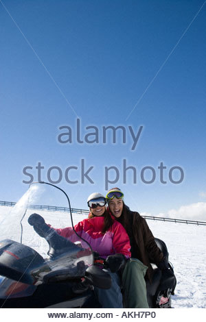 Friends on a snowmobile - Stock Photo