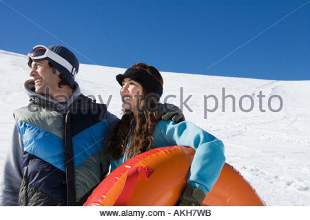 Couple with inflatable sledge - Stock Photo