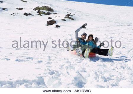 Couple riding on a snow tube - Stock Photo