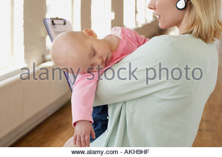 A mother holding sleeping baby - Stock Photo