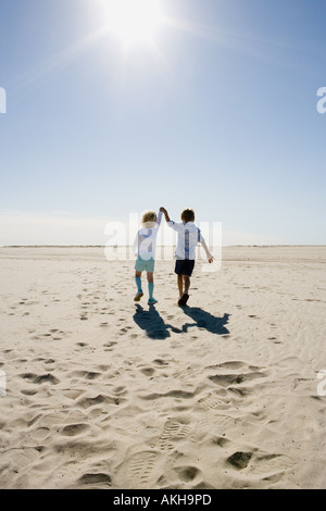 Boy and girl walking on beach holding hands - Stock Photo