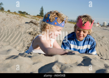 Children wearing paper crowns playing on beach - Stock Photo