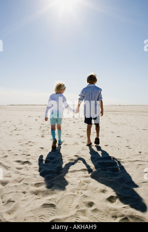 Boy and girl holding hands, walking on beach - Stock Photo