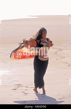 Carefree Asian woman on windy Hawaiian shore - Stock Photo