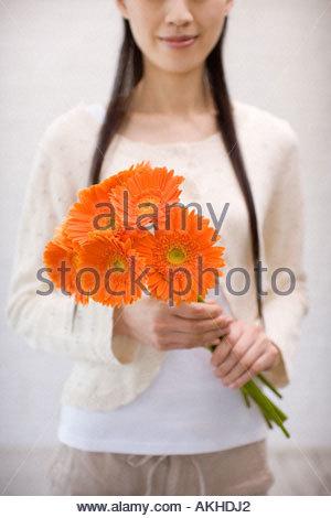 Woman holding gerberas - Stock Photo
