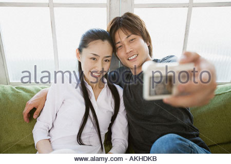 Couple taking a picture of themselves - Stock Photo