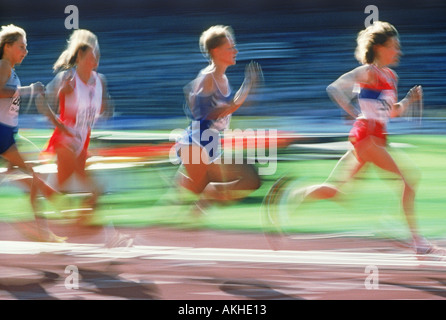 Female runners in track and field competition - Stock Photo
