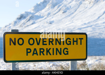 Yellow No overnight parking sign in Glencoe with out of focus snow covered mountain in background in Scottish highlands - Stock Photo
