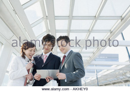 Colleagues looking at personal organiser - Stock Photo