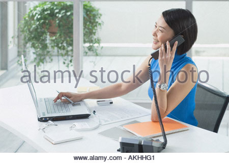 Asian businesswoman at her desk - Stock Photo