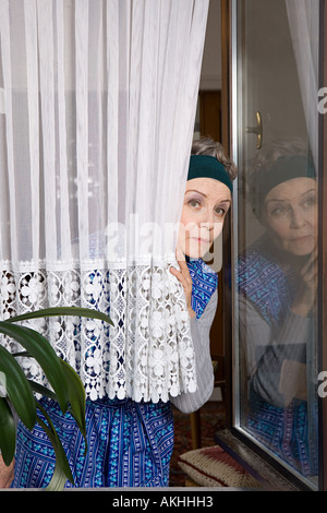 Woman peering around net curtain - Stock Photo