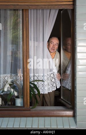 Senior peering around net curtain - Stock Photo