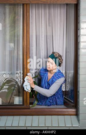 Woman dusting window frames - Stock Photo