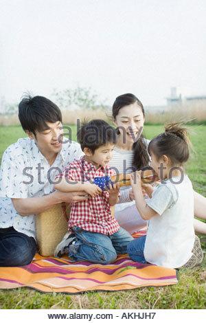 Asian family having a picnic - Stock Photo