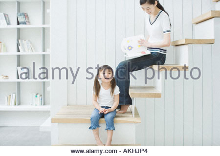 Mother and daughter sitting on stairs - Stock Photo
