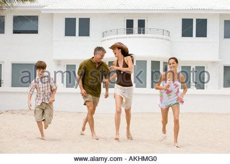 Family having fun outside beach house - Stock Photo