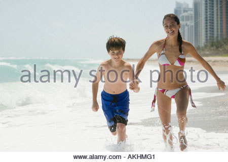 Brother and sister running in the sea - Stock Photo